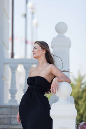 sleeveless dress: Portrait of girl in the park. Young long-haired woman in black sleeveless dress posing on open air looking away