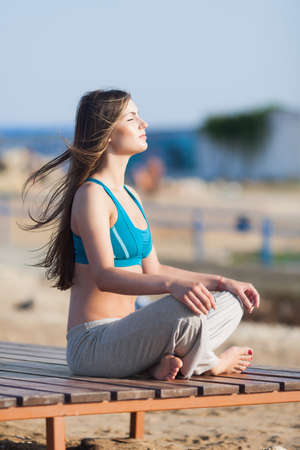 Athletic girl on beach. Barefoot young woman in sports bra sits cross-legged on open air with hands on knees. Side view, eyes closed photo