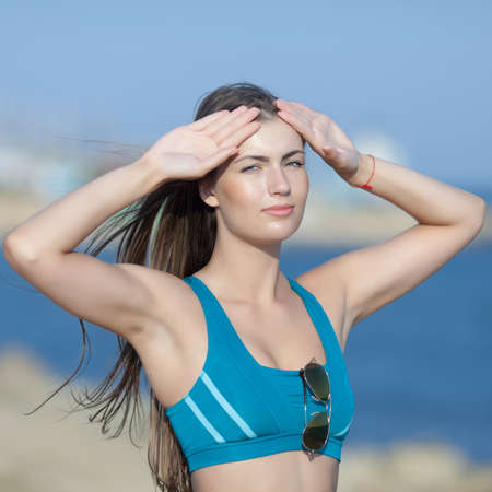 Sportswoman on open air. Waist up portrait of young long-haired woman in sports bra with arms raised. Girl looking at camera Stock Photo