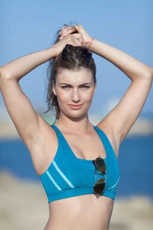 waist up: Athletic girl on open air. Young long-haired woman in sports bra adjusting hairstyle with arms raised. Waist up portrait, looking at camera