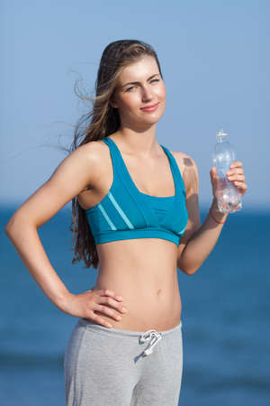 bra top: Athletic girl on open air. Attractive young woman in sports bra with plastic bottle in her hand looking at camera smiling