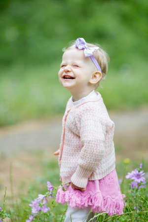 squint: Little girl laughing. Portrait of charming oneyearold girl in the park