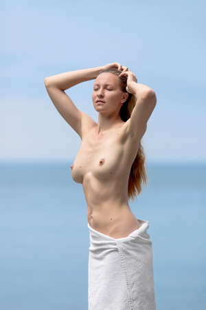 half naked: Portrait of topless young woman. Half naked female with a towel on the hips adjusts her hairstyle on the beach arms raised eyes closed