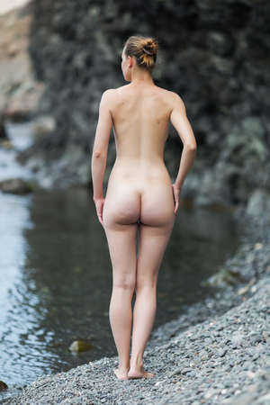 female nudity: Girl at the sea. Attractive naked young woman stands on rocky beach rear view