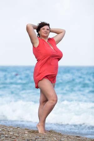 tetona: Mujer en rojo en el mar. Mujer joven con sobrepeso en la presentación blusa roja con los brazos levantados contra el mar