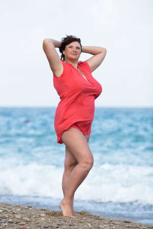 chubby: Woman in red at the sea. Overweight young woman in red blouse posing with arms raised against the sea