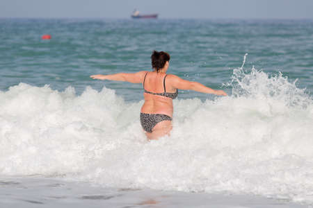 Woman in swimwear at the sea. Overweight young woman in swimsuit comes in water in time of surf, rear view Фото со стока