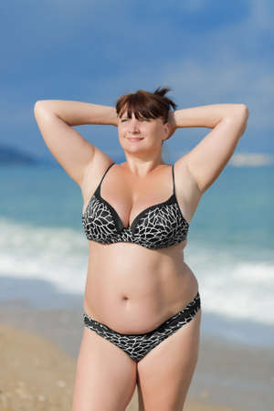 Vrouw in badkleding op de zee. Overgewicht jonge vrouw in zwembroek poseren met opgeheven armen tegen de zee