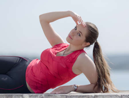 ponytail: Girl with ponytail poses outdoors. Young woman with arm raised lying on side looking at camera Stock Photo