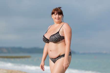 obeso: Mujer en traje de baño en el mar. Mujer joven con sobrepeso en traje de baño contra el mar. Ella mira a la cámara sonriendo