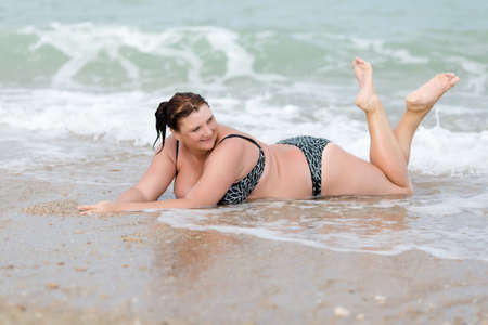 Woman in swimwear at the sea. Overweight young woman in swimsuit lying on front on wet sand in surf line