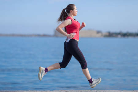 water bottle: Jogging. Young woman with water bottle runs along waterfront