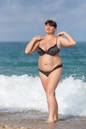 donne obese: Donna in costume da bagno al mare. Sovrappeso giovane donna in costume da bagno in posa contro il mare