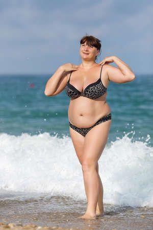 plump: Woman in swimwear at the sea. Overweight young woman in swimsuit posing against the sea