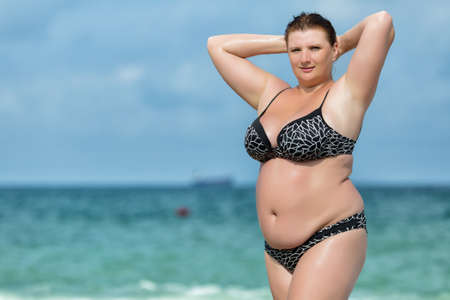 Woman in swimwear at the sea. Overweight young woman in swimsuit posing against horizon over water. Female with arms raised corrects her hair looking at camera