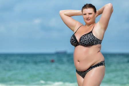 Vrouw in badkleding op de zee. Overgewicht jonge vrouw in zwembroek poseren tegen horizon over water. Vrouw met opgeheven armen corrigeert haar haar te kijken naar de camera Stockfoto