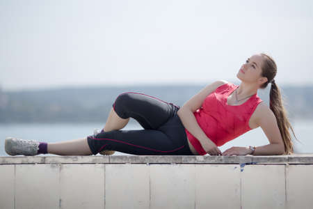 russian ethnicity caucasian: Girl with ponytail poses outdoors. Young woman in sportswear lying on side looking up Stock Photo