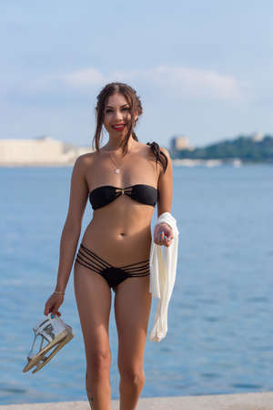 girl bra: Girl at the sea. Attractive young woman in black bikini walking along seashore with shoes and dress in her hands