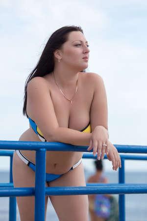 busty: Chica en el mar. mujer joven con sobrepeso en traje de baño en el paseo marítimo Foto de archivo