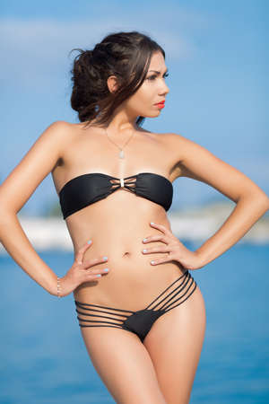 young woman in underwear: Girl at the sea. Hot sensual young brunette in skimpy black swimsuit against the sea Stock Photo