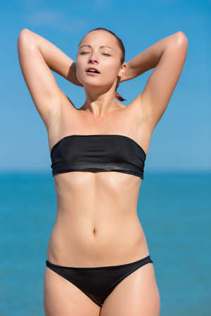 russian ethnicity: Girl on the beach. Young woman in black swimwear posing arms raised on seashore