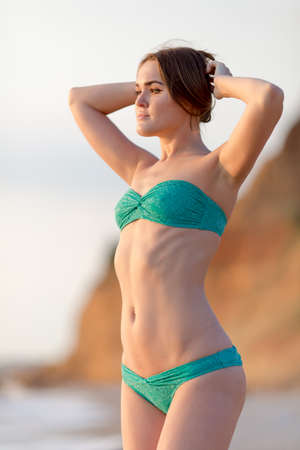 european ethnicity: Girl on the beach. Portrait of young woman in green bikini against the seashore. She posing arms raised looking into distance Stock Photo