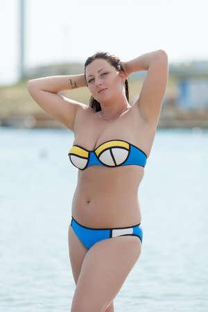 Vrouw in badkleding op de zee. Overgewicht jonge vrouw in zwempak tegen de zee Stockfoto