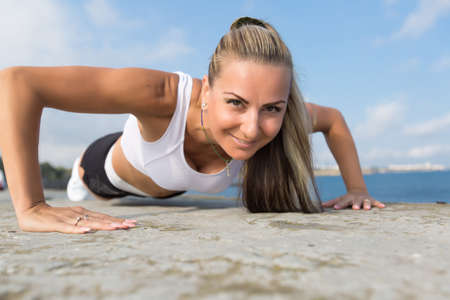 in the open air: Female doing exercises on open air. Middle age woman doing push ups outdoors.