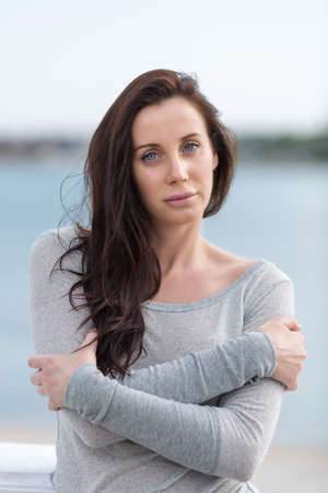in the open air: Long haired brunette on open air. Portrait of attractive young woman in gray sportswear. She posing arms folded looking at camera