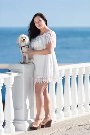 racy: Girl with dog on seafront. Young woman with chinese crested dog on the background of the sea