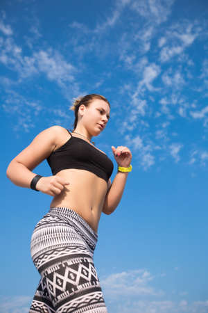 foreshortening: Jogging. Sportswoman runs against the sky