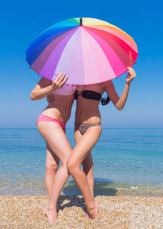 waist down: Girls at the sea. Two young women hiding under the iridescent parasol