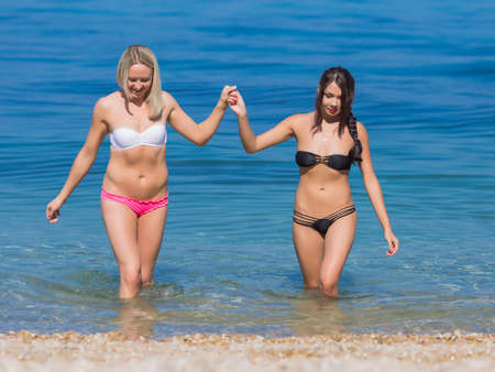 come in: Girls at the sea. Two young women in swimwears walking hand in hand in water