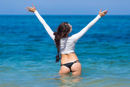back  view: Girl at the sea. Slim brunette in white crop top with long sleeves stands in water with arms raised looking up Stock Photo