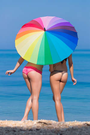 Girls under the rainbow umbrella. Two young women hiding from the sun under the iridescent parasol Stock Photo