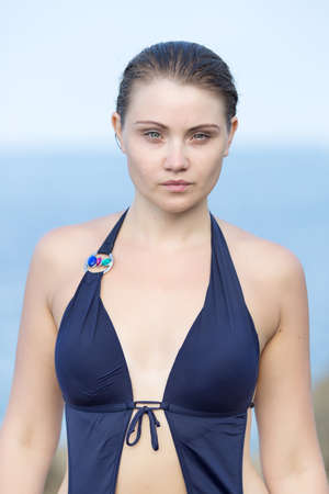 slicked: Portrait of girl after swimming. Wet young woman in one-piece swimsuit looking at camera