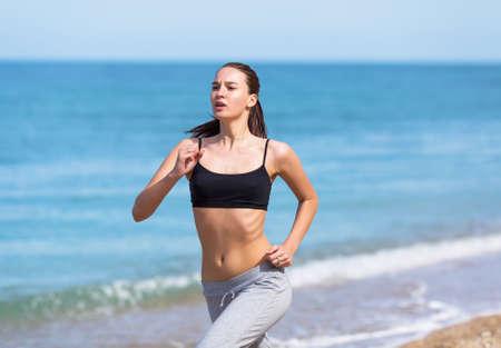 Jogging. Young woman runs along seashore