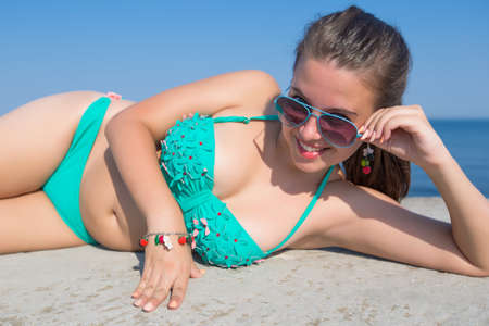 Girl at the sea. Attractive young woman in swimwear lying down looking at camera over tinted sunglasses