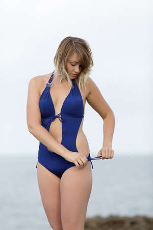 russian ethnicity: Girl at the sea. Blond woman in one-piece swimsuit adjusting it looking down Stock Photo