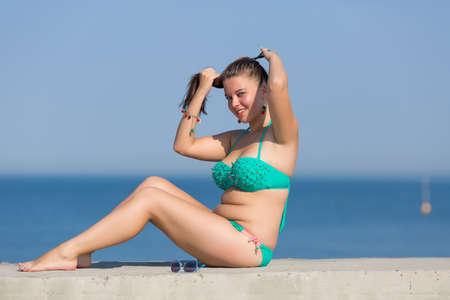 Meisje bij de zee. Overgewicht jonge vrouw zit op betonnen pier en maakt kapsel