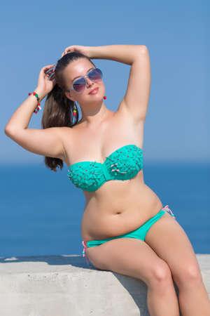 donne obese: Ragazza al mare. Sovrappeso giovane donna in occhiali da sole si siede sul molo di cemento e fa l'acconciatura Archivio Fotografico