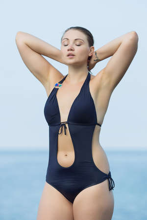 arms behind head: Girl on the beach. Young woman in dark blue swimwear posing arms raised on seashore Stock Photo