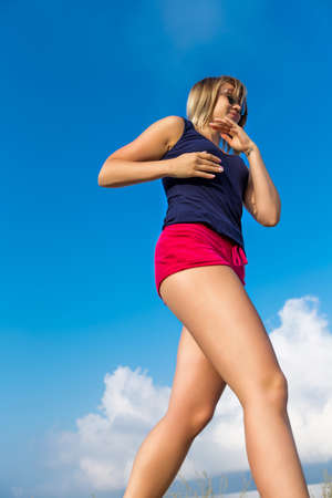 foreshortening: Jogging against the sky. Young woman in red shorts and sunglasses runs on open air