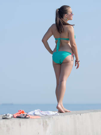 Girl at the sea. Overweight young woman in swimwear on seafront, rear view