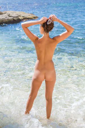 female nudity: Girl at the sea. Naked young woman enters the sea water, rear view