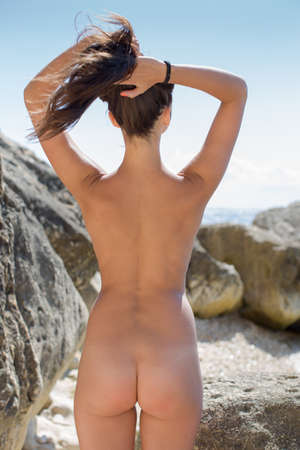 nude nature: Girl on rocky seashore. Naked young woman posing on the beach with arms raised, rear view Stock Photo