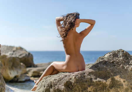 Girl on seashore. Naked young woman sits on rock and corrects her hairstyle, rear view