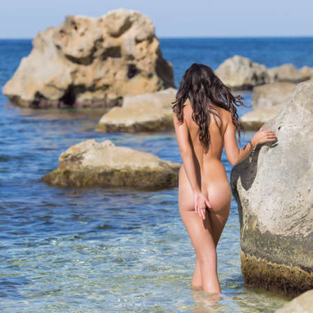 nude nature: Girl at the sea. Naked young woman enters the sea, rear view