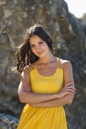 yellow dress: Portrait of girl in yellow dress. Young woman posing on the rocky seashore looking at camera smiling