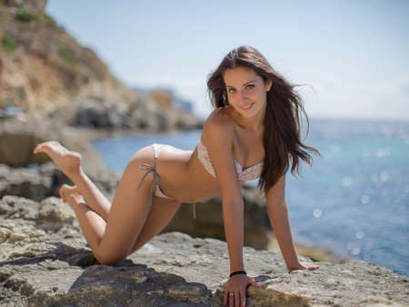 eastern european ethnicity: Girl on rocky seashore. Young woman in bikini posing on the beach looking at camera smiling